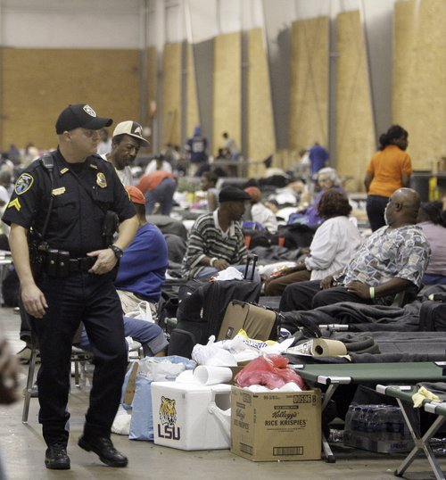 Police officer walks inside a shelter set up for evacuees from Hurricane Gustav in Shreveport, La., Tuesday, Sept. 2, 2008. Many of the people that fled the storm are complaining about sub-standard facilities devoid of any Red Cross or FEMA aid.  (AP Photo/LM Otero)
