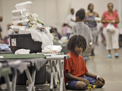 A child plays next to a full garbage can at a shelter set up for evacuees from Hurricane Gustav in Shreveport, La., Tuesday, Sept. 2, 2008. Many of the people that fled the storm are complaining about sub standard facilities devoid of any Red Cross or FEMA aid.  (AP Photo/LM Otero)