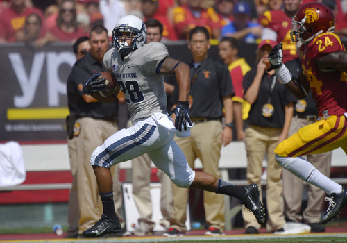 Utah State running back Joey DeMartino, left, rushes for 55 yards as Southern California safety Demetrius Wright gives chase during the first half of an NCAA college football game, Saturday, Sept. 21, 2013, in Los Angeles. (AP Photo/Mark J. Terrill)