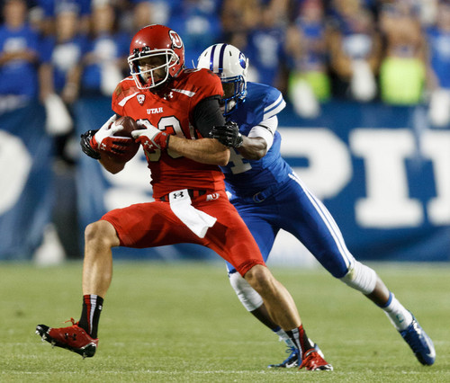 Trent Nelson  |  The Salt Lake Tribune Utah Utes wide receiver Sean Fitzgerald (83) is pulled down by Brigham Young Cougars defensive back Robertson Daniel (4) in the first quarter as the BYU Cougars host the Utah Utes, college football Saturday, September 21, 2013 at LaVell Edwards Stadium in Provo.