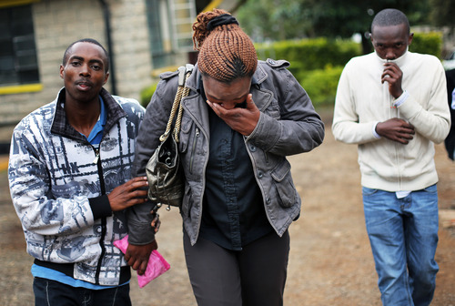 Zipporah Mureithi, 34, centre, is helped by relatives as she weeps after identifying the body of her father Paul, 56, at the city morgue in Nairobi, Kenya, Tuesday Sept. 24 2013.  Paul was one of the victims of the Westgate Mall hostage siege. Kenyan security forces are still combing the Mall on the fourth day of the siege by al-Qaida-linked terrorists. (AP Photo/ Jerome Delay)
