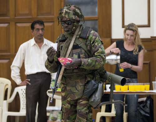 A Kenya Defence Force soldier heavily armed as he carries an anti tank launcher on his back, as he takes a break to have snack at Oshwal Centre near the Westgate Mall in Nairobi, Kenya, Tuesday, Sept. 24, 2013.  Kenyan security forces battled al-Qaida-linked terrorists in an upscale mall for a fourth day. Another explosion and more gunfire could be heard coming from the mall in the early hours of Tuesday morning.(AP Photo/Sayyid Azim)