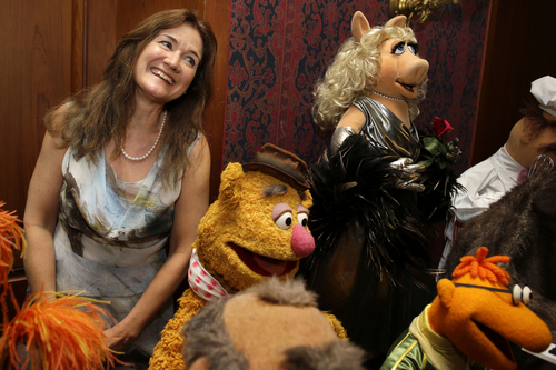 """Cheryl Henson, daughter of Jim Henson, left, is surrounded by """"muppets"""" after donating additional Jim Henson objects to the Smithsonian's National Museum of American History, including, from left, Fozzie Bear, Miss Piggy, and Scooter, from The Muppet Show, during a ceremony at the Smithsonian's National Museum of American History in Washington, Tuesday, Sept. 24, 2013. Miss Piggy is finally joining Kermit the Frog in the Smithsonian Institution's collection of Jim Henson's Muppets, and Bert and Ernie will have a place in history, too. Henson's daughter, Cheryl Henson, is donating 20 more puppets and props to the National Museum of American History. (AP Photo/Jacquelyn Martin)"""