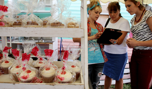 "Keith Johnson | The Salt Lake Tribune  Cake Farm co-owner Courtney Post (left) discusses wedding cake options with customers Christina (center) and Juliana Bischoff at the Cake Farm roadside stand located along the ""Utah Fruitway"" in Perry, September 14, 2013."