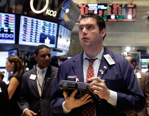 In this Wednesday, Sept. 25, 2013, photo, trader Robert McQuade works on the floor of the New York Stock Exchange. Worries about the U.S. economy and a looming budget battle in Washington kept global stock markets in check Thursday Sept. 26, 2013. (AP Photo/Richard Drew)