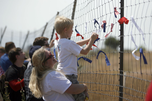 Francisco Kjolseth  |  The Salt Lake Tribune Red, white and blue ribbons are tied to the outer perimeter fence of the new NSA Data Center as opponents of the facility protest on the 4th of July.