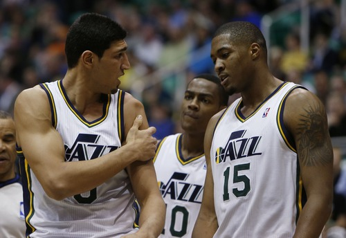 Steve Griffin   The Salt Lake Tribune   Utah's Elec Burks and Derrick Favors, right, look at Enes Kanter as he holds his dislocated shoulder following scramble for a loose ball  during first half action in the Jazz versus Suns NBA game at EnergySolutions Arena in Salt Lake City, Utah Wednesday March 27, 2013. Kanter dislocated his shoulder on the play and left the game.