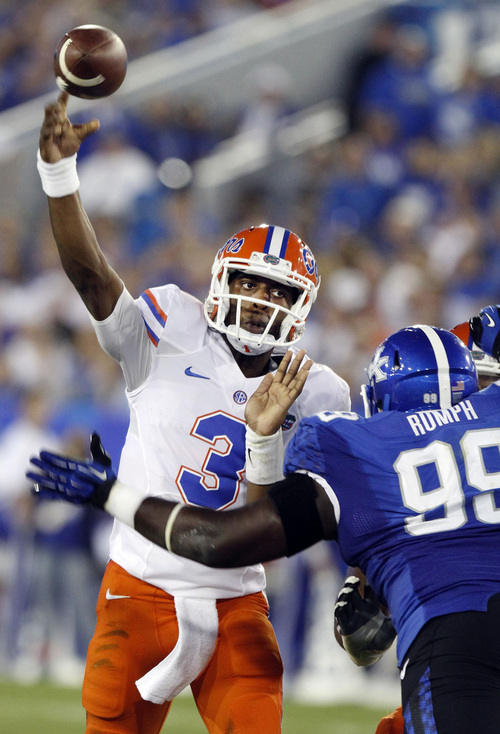 Florida quarterback Tyler Murphy (3) throws under pressure from Kentucky's Donte Rumph (99) in the second quarter of an NCAA college football game on Saturday, Sept. 28, 2013, in Lexington, Ky. (AP Photo/James Crisp)