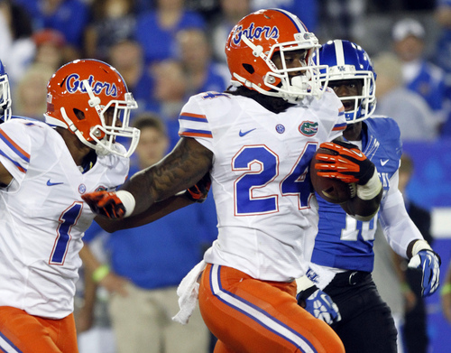 Florida's Matt Jones (24) and Quinton Dunbar (1) collide as they try to evade Kentucky's Marcus McWilson, right, in the  second quarter of an NCAA college football game on Saturday, Sept. 28, 2013, in Lexington, Ky. (AP Photo/James Crisp)