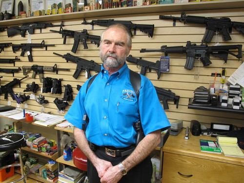 Frank Loane, owner of Pasadena Pawn and Gun, stands in front of a wall of assault rifles at his store in Pasadena, Md., on Thursday, Sept. 26, 2013. Loane, who said he has seen significant boost in business this year as Maryland lawmakers debated and passed a sweeping gun-control bill, won't be able to sell many of the guns shown behind him in Maryland after Tuesday, when the gun-control law takes effect banning 45 types of assault weapons. Loane also says handgun sales have been up, because customers don't want to meet a new fingerprinting requirement to buy a handgun on Oct. 1, as well as additional paperwork and a gun safety course. (AP Photo/Brian Witte)