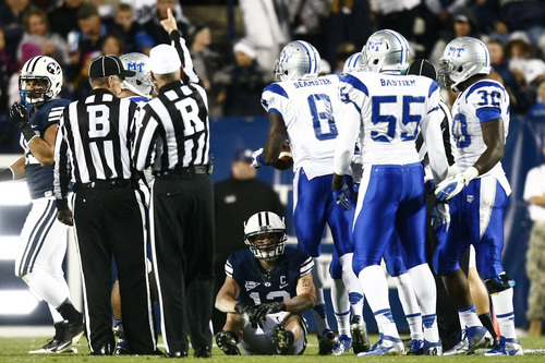 Chris Detrick  |  The Salt Lake Tribune Brigham Young Cougars wide receiver JD Falslev (12) remains on the ground after Middle Tennessee Blue Raiders cornerback Sammy Seamster (8) recovered a fumble during the first half of the game at LaVell Edwards Stadium Friday September 27, 2013. BYU is winning the game 23-10 at halftime.