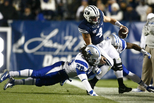 Chris Detrick  |  The Salt Lake Tribune Brigham Young Cougars quarterback Taysom Hill (4) is tackled by Middle Tennessee Blue Raiders linebacker Christian Henry (28) and Middle Tennessee Blue Raiders linebacker Leighton Gasque (40) during the first half of the game at LaVell Edwards Stadium Friday September 27, 2013. BYU is winning the game 23-10 at halftime.
