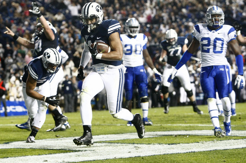 Chris Detrick  |  The Salt Lake Tribune Brigham Young Cougars running back Michael Alisa (42) runs past Middle Tennessee Blue Raiders safety Kevin Byard (20) and Middle Tennessee Blue Raiders linebacker Stephen Roberts (30) for a touchdown during the first half of the game at LaVell Edwards Stadium Friday September 27, 2013. BYU is winning the game 23-10 at halftime.