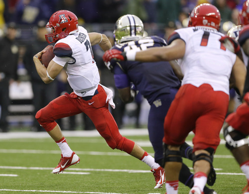 Arizona quarterback B.J. Denker, left, breaks away for a 33-yard run against Washington that set up a touchdown in the first half of an NCAA college football game, Saturday, Sept. 28, 2013, in Seattle. (AP Photo/Ted S. Warren)