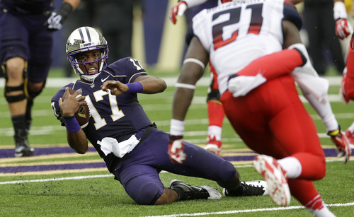 Washington quarterback Keith Price (17) slides after keeping the ball in the first half of an NCAA college football game against Arizona, Saturday, Sept. 28, 2013, in Seattle. (AP Photo/Ted S. Warren)