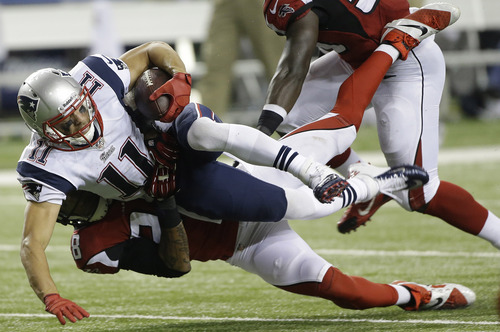 New England Patriots wide receiver Julian Edelman (11) falls to the turf against Atlanta Falcons free safety Thomas DeCoud (28) during the second half of an NFL football game, Sunday, Sept. 29, 2013, in Atlanta. (AP Photo/John Bazemore)