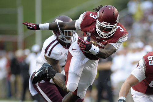 Arkansas running back Alex Collins (3) gains yardage against Texas A&M linebacker Nate Askew during the first quarter of an NCAA college football game in Fayetteville, Ark., Saturday, Sept. 28, 2013. (AP Photo/Beth Hall)