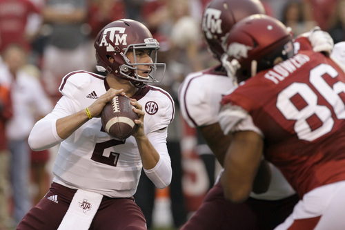 Texas A&M quarterback Johnny Manziel (2) looks for a receiver as he prepares to pass over Arkansas defensive end Trey Flowers (86) during the first quarter of an NCAA college football game in Fayetteville, Ark., Saturday, Sept. 28, 2013. (AP Photo/Danny Johnston)