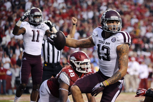 Texas A&M wide receiver Mike Evans (13) and wide receiver Derel Walker (11) celebrate Evans' touchdown over Arkansas defensive end Deatrich Wise Jr. (48) during the seconod quarter of an NCAA college football game in Fayetteville, Ark., Saturday, Sept. 28, 2013. (AP Photo/Beth Hall)