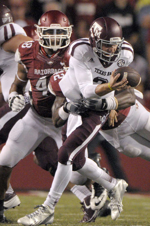 Texas A&M quarterback Johnny Manziel (2) is sacked by Arkansas defensive end Chris Smith (42) assisted by defensive end Deatrich Wise Jr. (48) during the second quarter of an NCAA college football game in Fayetteville, Ark., Saturday, Sept. 28, 2013. (AP Photo/David Quinn)