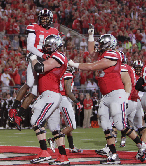 Ohio State wide receiver Corey Brown, top, celebrates his touchdown against Wisconsin with teammates during the second quarter of an NCAA college football game Saturday, Sept. 28, 2013, in Columbus, Ohio. (AP Photo/Jay LaPrete)