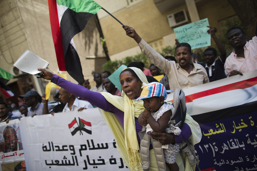 """Sudanese people chant slogans against longtime President Omar al-Bashir during a protest in front of the Sudanese embassy in Cairo, Egypt, Sunday, Sept. 29, 2013. Sudanese security forces in pickup trucks opened fire Saturday, Sept. 28 on hundreds of mourners marching after the funeral of a protester killed a day earlier, the latest violence in a week of demonstrations calling for the ouster of al-Bashir. Partial translation of Arabic on the banner, bottom left, reads, """"Peace and justice, the people's will."""" (AP Photo/Hassan Ammar)"""