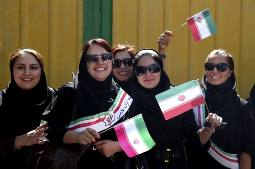Supporters of Iranian President Hassan Rouhani, wave Iranian flags, upon his arrival from the U.S. near the Mehrabad airport in Tehran, Iran, Saturday, Sept. 28, 2013. Iranians from across the political spectrum hailed Saturday the historic phone conversation between President Barack Obama and Rouhani, reflecting wide support for an initiative that has the backing of both reformists and the country's conservative clerical leadership. (AP Photo/Ebrahim Noroozi)