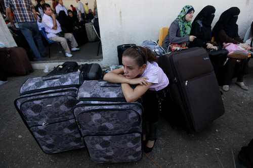 A Palestinian girl rests on her luggage as she and her family wait to cross into Egypt from Gaza at the Rafah border crossing in the southern Gaza Strip, Sunday, Sept. 29, 2013. Egyptian and Palestinian officials say the main border crossing in the Gaza Strip will be reopened to passenger traffic for several days. Egypt has opened the Rafah border only intermittently following the coup that ousted former President Mohammed Morsi, and traffic was limited at times to students and those seeking medical care. (AP Photo/Hatem Moussa)