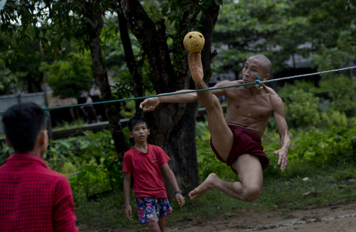 A Buddhist monk kicks a rattan ball during a game of Chinlone in Kawhmu, southwest of Yangon, Myanmar, Sunday, Sep 29, 2013. Popular Burmese sport Chinlone, a combination of sport and dance is played between two teams, each team consists of six players, passing a rattan ball back and forth with feet, knees and heads. (AP Photo/Gemunu Amarasinghe)