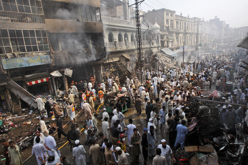 Pakistani rescue workers, police officers and civilians gather at the site of a car bomb explosion in Peshawar, Pakistan, Sunday, Sept. 29, 2013. A deadly car bomb exploded on a crowded street in northwestern Pakistan Sunday, in the third blast to hit the troubled city of Peshawar in a week, officials said. (AP Photo/Mohammad Sajjad)