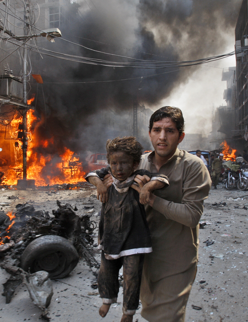 A Pakistani man carrying a child rushes away from the site of a blast shortly after a car bomb exploded in Peshawar, Pakistan, Sunday, Sept. 29, 2013. A deadly car bomb exploded on a crowded street in northwestern Pakistan Sunday, in the third blast to hit the troubled city of Peshawar in a week, officials said. (AP Photo/Mohammad Sajjad)
