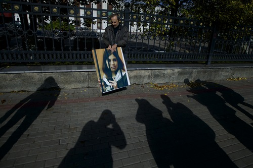 Russian journalist Alexander Podrabinek holds a portrait of jailed Pussy Riot punk group member Nadezhda Tolokonnikova, with shadows of reporters in front, during a protest outside of the Federal Prison Administration headquarter in Moscow, Wednesday, Sept. 25, 2013. Alexander Podrabinek held a protest in support of imprisoned Nadezhda Tolokonnikova who declared a hunger strike on Monday to protest against what she described as inhumane working conditions and threats to her life at a women's penal colony. (AP Photo/Ivan Sekretarev)