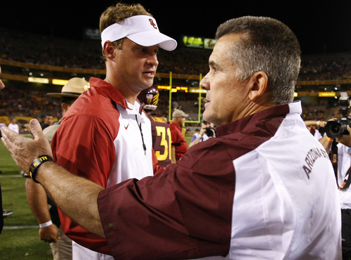 FILE - Southern California head coach Lane Kiffin shakes hands with Arizona State head coach Todd Graham after an NCAA college football game in a Saturday, Sept. 28 2013 file photo, in Tempe, Ariz. USC has fired football coach Lane Kiffin, the Trojans announced early Sunday, Sept. 29, 2013. Kiffin went 28-15 at USC in parts of four seasons, but his club has dropped seven of its last 11 games overall and is winless in a pair of Pac-12 games so far this year.  (AP Photo/Rick Scuteri, File)