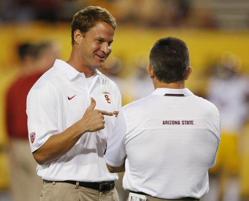 """FILE - Southern California coach Lane Kiffin talks to Arizona State coach Todd Graham before an NCAA college football game in a Saturday, Sept. 28 2013, file photo, in Tempe, Ariz. USC has fired football coach Lane Kiffin, the Trojans announced early Sunday, Sept. 29, 2013. Athletic director Pat Haden said in a short news release that he informed Kiffin of the decision """"upon the team charter's arrival back in Los Angeles early Sunday morning following USC's 62-41 loss at Arizona State.""""  (AP Photo/Rick Scuteri, File)"""