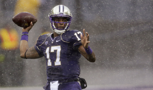 Washington quarterback Keith Price passes in the rain during the first half of an NCAA college football game against Arizona, Saturday, Sept. 28, 2013, in Seattle. (AP Photo/Ted S. Warren)