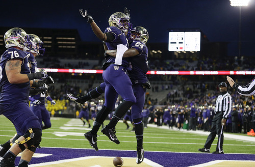 Ted S. Warren | The Associated Press Washington running back Jesse Callier (24) celebrates with Washington's Kevin Smith, center left, after Callier scored a touchdown late in the fourth quarter of an NCAA college football game against Arizona, Saturday, Sept. 28, 2013, in Seattle. Washington won 31-13. (AP Photo/Ted S. Warren)