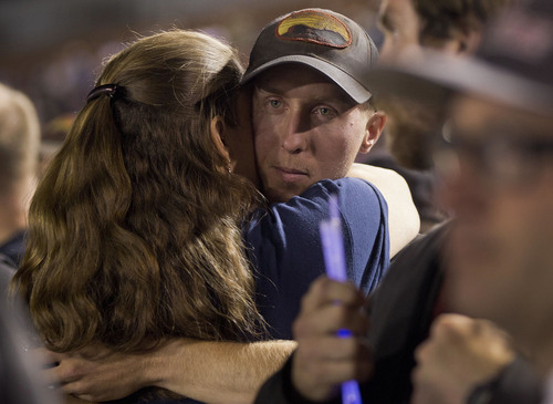 FILE - In this July 2, 2013 file photo, firefighter Brendan McDonough embraces a mourner near the end of a candlelight vigil in Prescott, Ariz. McDonough was the sole survivor of the 20-man Granite Mountain Hotshot Crew after an out-of-control blaze killed the 19 near Yarnell, Ariz. Investigators are set to release a report Saturday, Sept. 28, 2013, on the deaths of the 19 elite firefighters who became trapped by flames in a brush-choked canyon north of Phoenix.(AP Photo/Julie Jacobson, File)