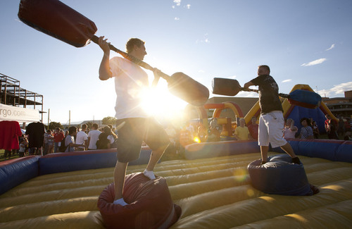 Dylan Wyllie, left, and Chris Bills try to knock each otehr from their perches during the Dixie State College welcome week carnival Monday, Aug. 22, 2011 on the campus of Dixie State College. Jud Burkett / The Spectrum