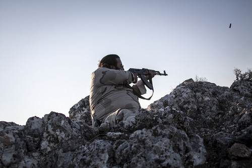 In this Sunday, Sept. 29, 2013 photo, a Free Syrian Army fighter aims his weapon towards government forces during clashes in Telata village, a frontline located at the top of a mountain in the Idlib, a northwest province countryside of Syria. (AP Photo)