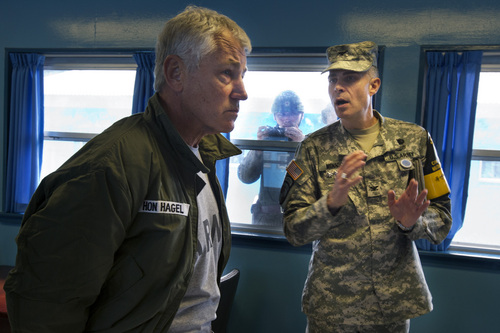 U.S. Secretary of Defense Chuck Hagel, left, listens to U.S. Army Col. James Minnich, as a North Korean soldier, center, takes a photograph through a window at a UN truce village building that sits on the border of the Demilitarized Zone (DMZ), the military border separating the two Koreas, in Panmunjom, South Korea, on Monday, Sept. 30, 2013. (AP Photo/Jacquelyn Martin, Pool)