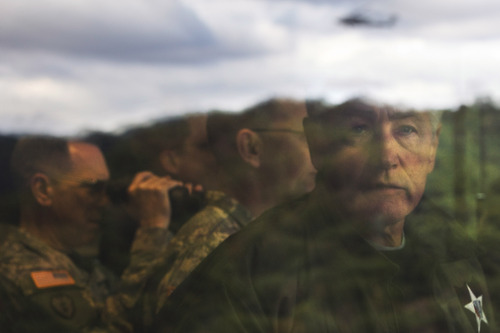 U.S. Secretary of Defense Chuck Hagel looks out a window as he observes training, including an Apache helicopter, reflected on the glass, at the Rodriguez Live Fire Complex (RLFC), a few miles from the Demilitarized Zone (DMZ), the military border separating the two Koreas, in South Korea, on Monday, Sept. 30, 2013. Hagel is expected to spend time in South Korea before heading to Japan for ministerial meetings. (AP Photo/Jacquelyn Martin, Pool)