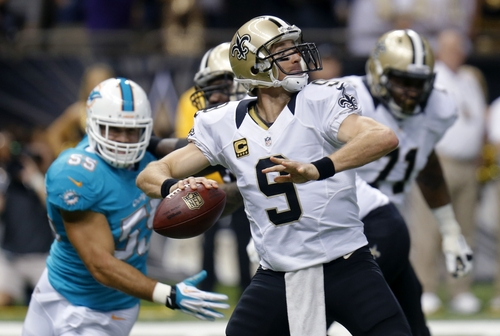 New Orleans Saints quarterback Drew Brees (9) passes as Miami Dolphins outside linebacker Koa Misi (55) rushes in the first half of an NFL football game in New Orleans, Monday, Sept. 30, 2013. (AP Photo/Bill Haber)