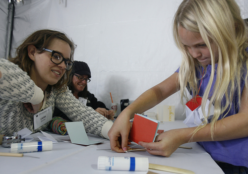 Scott Sommerdorf   |  The Salt Lake Tribune Volunteer Laura Decker with the Library's book arts program helps Kasey Byrd, 8 years, with a book-binding exercise at the 16th annual Book Festival, sponsored by the Utah Humanities Council. The event is a two-day outdoor festival taking place on Library Square Saturday and Sunday that includes authors, music, book arts, a poetry slam, writing activities and more, Saturday, September 28, 2013.
