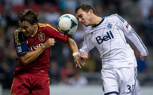 Vancouver Whitecaps' Russell Teibert, right, gets his head on the ball as Real Salt Lake's Cole Grossman defends in front of his goal during the first half of an MLS soccer game Saturday, Sept.  28, 2013, in Vancouver, British Columbia. (AP Photo/The Canadian Press, Darryl Dyck)