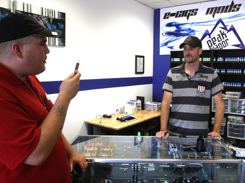 Rick Egan  | The Salt Lake Tribune   Corey Peay purchases flavors for his e-cigarette from Jake Simpson, owner of Peak Vapor, Monday, September 30, 2013. Peay purchased  PB & Chocolate, Gummi Bear, and Rockstar flavored liquid for his e-cigarette.