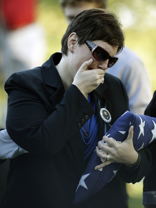 Jamie Bradway, wife of slain IMPD officer Rod Bradway, cries following a funeral service on Thursday, Sept. 26, 2013, in Indianapolis. Bradway was killed while responding to a domestic disturbance last Friday. (AP Photo/Darron Cummings)