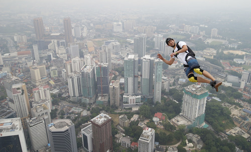 Base jumper Kristian Moxnes of Norway leaps from the 300-meter Open Deck of the Malaysia's landmark Kuala Lumpur Tower during the International Tower Jump in Kuala Lumpur, Friday, Sept. 27, 2013. About 103 professional base jumpers from 20 countries took part in the annual event. (AP Photo/Vincent Thian)