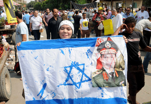 A supporter of Egypt's ousted President Mohammed Morsi holds a representation of the Israeli flag with a picture of Defense Minister Gen. Abdel-Fattah el-Sissi at a demonstration in Helwan, a suburb of Cairo, Egypt, Friday, Sept. 27, 2013. Morsi supporters held scattered protests, denouncing the popular-backed coup that ousted the Islamist president. Their protests have witnessed a sharp decrease in numbers, after a heavy security crackdown that left at least hundreds of dead.  (AP Photo/Mohammed Asad)