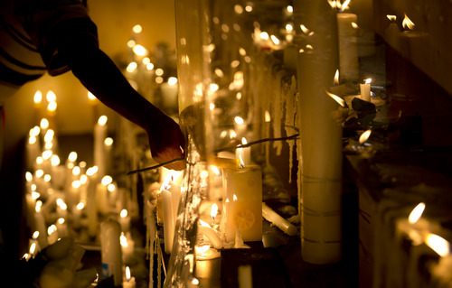 A Kenyan lights a candle to pay their respects as they and others came together to to light candles, sing and pray marking one week since the terrorist attack that killed 67 people, in front of the Westgate Mall in Nairobi, Kenya,  Saturday, Sept. 28, 2013. (AP Photo/Ben Curtis)