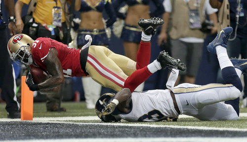 San Francisco 49ers safety Donte Whitner, top, intercepts a pass while St. Louis Rams wide receiver Brian Quick, bottom, defends as Whitner falls into the end zone for a touchback during the second quarter of an NFL football game Thursday, Sept. 26, 2013, in St. Louis. (AP Photo/Charlie Riedel)